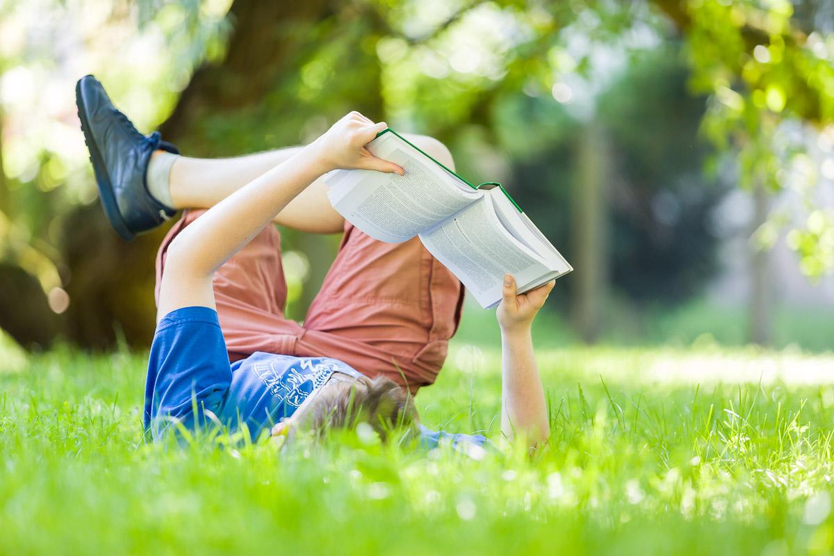 Student leżący na trawie, czytający książkę